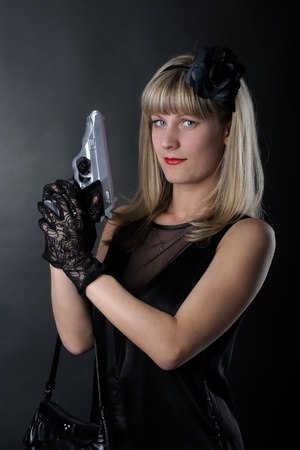 Gangster woman with pistol in black photo