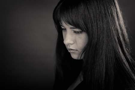 Portrait of brunette girl on dark background photo