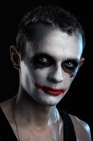 Spooky man joker on black background photo