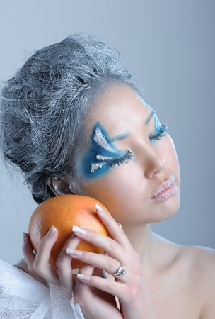Portrait of woman with creative makeup and orange in her hands photo