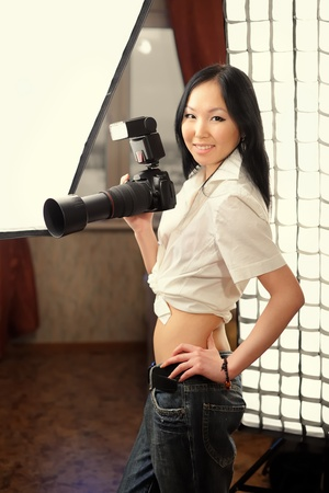 Young beautiful girl with photo camera in studio photo