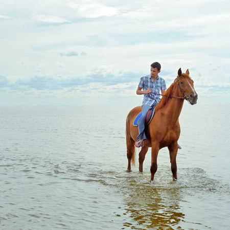 Man riding on a brown horse photo