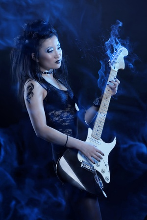 Woman rock star with guitar on dark background photo