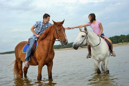 Mann und eine Frau im Meer auf dem Pferderücken