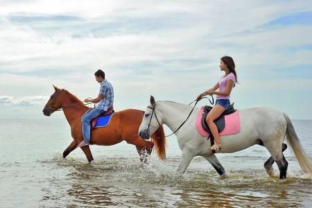 Man and a woman in the sea on horseback Stock Photo