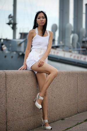 Asian woman near the wall outdoors photo