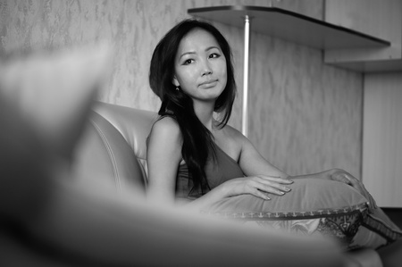 Smiling asian woman sitting on the sofa photo