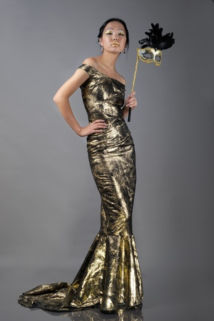Asian woman with carnaval mask in golden evening dress 版權商用圖片