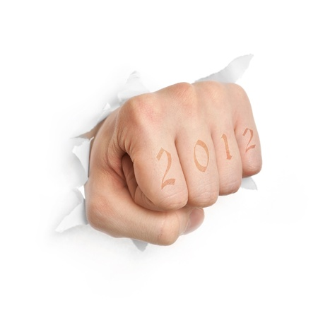 Hand with 2012 tattoo punching through paper isolated on white background  photo