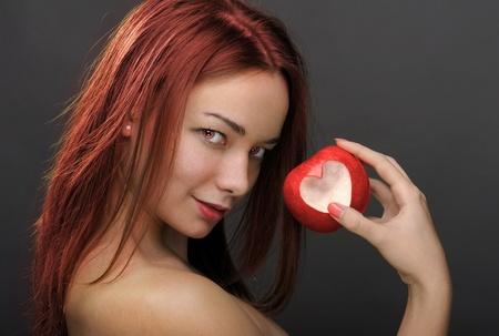 Woman with heart shape bitten apple photo