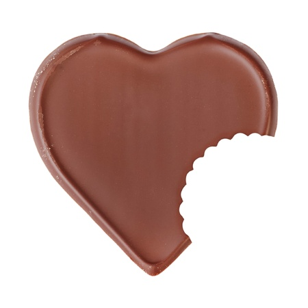 Bitten chocolate heart shape on white background photo