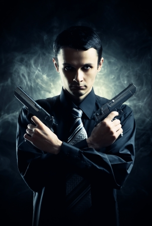 dual: Killer with two pistols on dark background Stock Photo