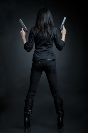 Asian woman with a pistol Banque d'images
