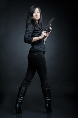 mujer con pistola: Mujer asiática con una pistola Foto de archivo