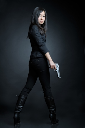 female assassin: Asian woman with a pistol Stock Photo