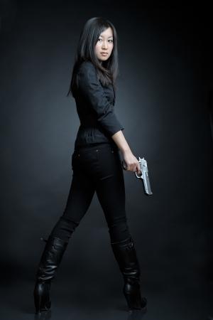 mujer con arma: Mujer asiática con una pistola Foto de archivo
