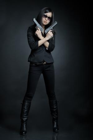 Asian woman with a pistol 免版税图像