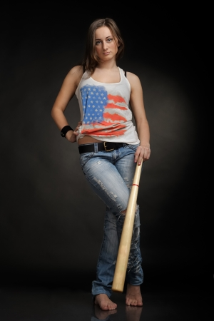 Woman with baseball bat on black background photo