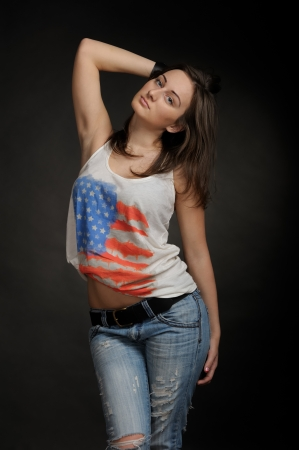 Woman in jeans and t-shirt on black background photo
