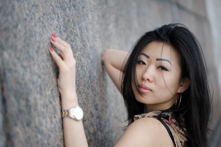 Portrait of asian woman near the wall photo