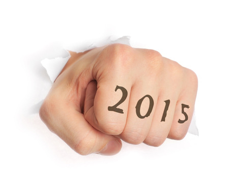 Hand with 2015 tattoo punching through paper isolated on white photo