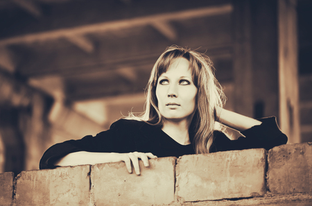 recline: Blonde woman recline on brick wall