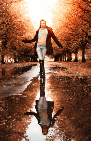 Woman walking in park at autumn photo