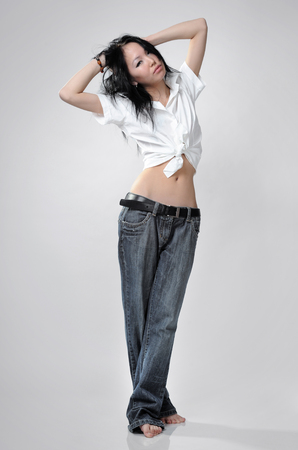Girl in tall jeans on white backgroud photo