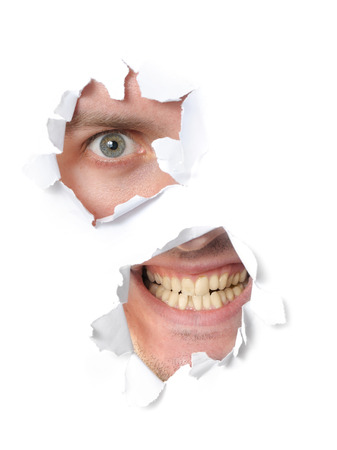 Spooky man looking through a hole in paper photo