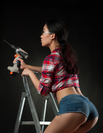 Sexy woman worker on ladder Stock Photo
