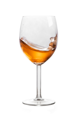 Glass of alcohol in motion isolated on white background