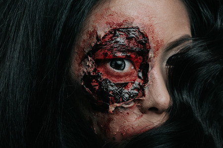 Close-up portrait of a horrible scary zombie woman with bloody eye, horror Halloween makeup. 版權商用圖片 - 111256111