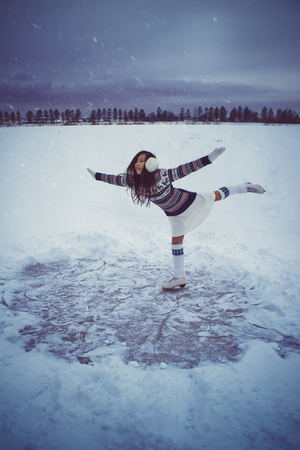 Girl skating outdoors at winter with snow