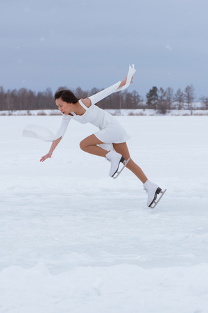 Pretty young woman on skates in white dress at winter frozen park outdoors Stock Photo