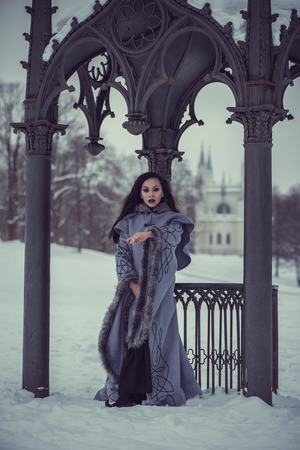 Fairytale of young woman dressed in long sleeved coat at winter with snow outdoors Stock Photo