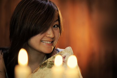 Asian woman indoor on bed with candles Stockfoto