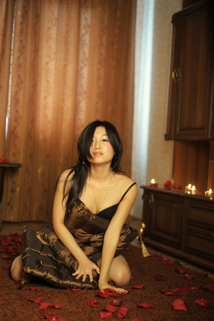 Sexual asian woman in lingerie sitting on carpet Imagens