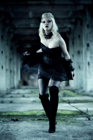 Gothic witch woman with spooky make-up in black dress