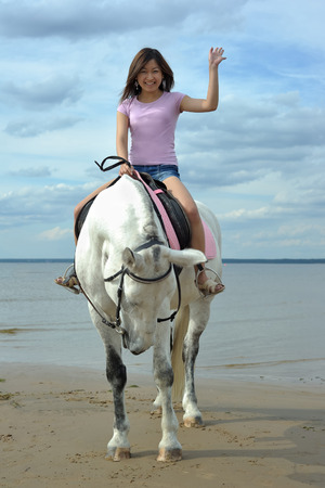 Young asian woman riding white horse on the beach Imagens