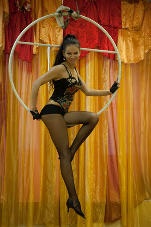 Cute girl doing exercises on the gymnastic ring indoors