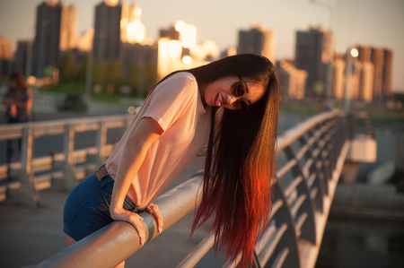 Asian girl in sunglasses leaning on the railing outdoors 版權商用圖片