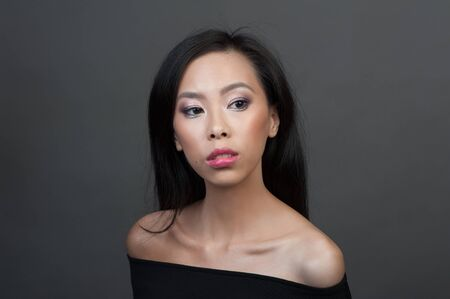Studio portrait of young asian woman over grey background