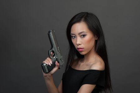 Young woman in black dress with pistol at studio