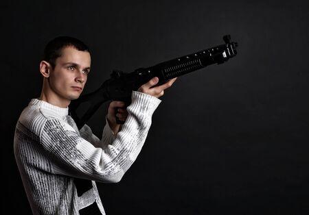 Young man with big gun at studio dark background