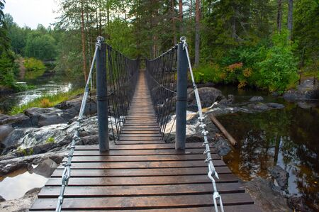 Suspension cable bridge crossing the river, ferriage in the woods