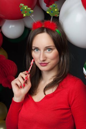 Woman with Christmas candy with balloons on background