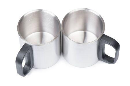 Empty metal mugs isolated on white background