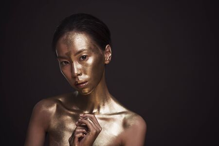 Beautiful young asian woman with bronze paint on her body at studio against dark background