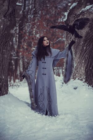 Fairytale of young woman dressed in long sleeved coat at winter with snow outdoors 스톡 콘텐츠