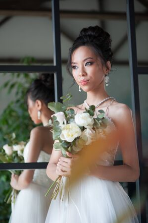 Asian bride with flowers in white dress. Indoor room back to mirror